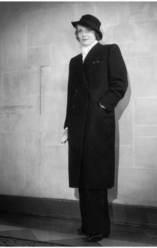 Marlene Dietrich in einem Herrenmantel und Hose