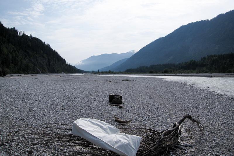 Flussbett der Isar mit alten Koffern